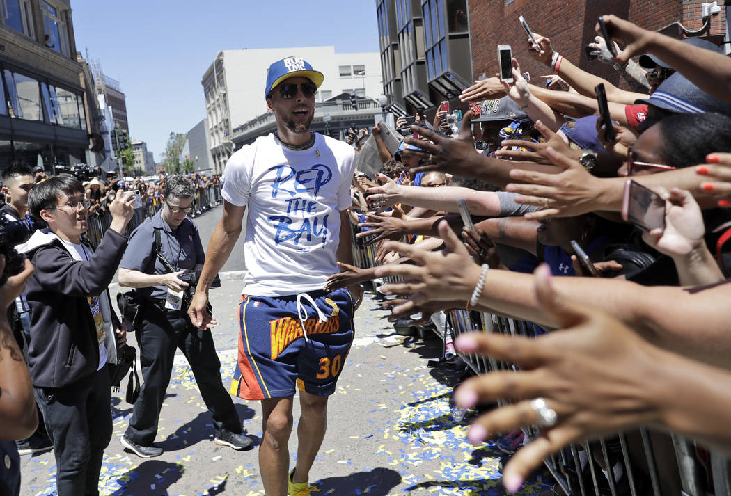 Golden State Warriors' Stephen Curry celebrates with fans during the team's NBA basketball championship parade, Tuesday, June 12, 2018, in Oakland, Calif. (AP Photo/Marcio Jose Sanchez)