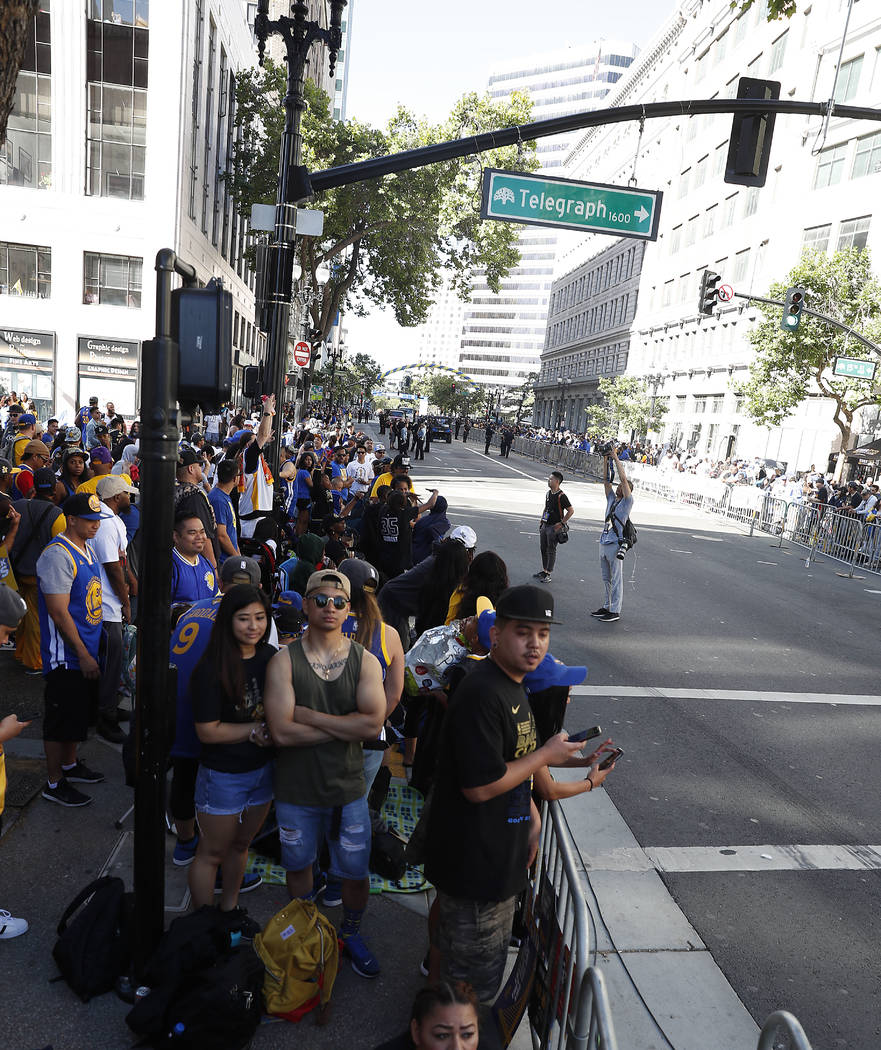 Fans line the streets as they wait for the parade to start in honor of the NBA basketball champion Golden State Warriors, Tuesday, June 12, 2018, in Oakland, Calif. (AP Photo/Tony Avelar)