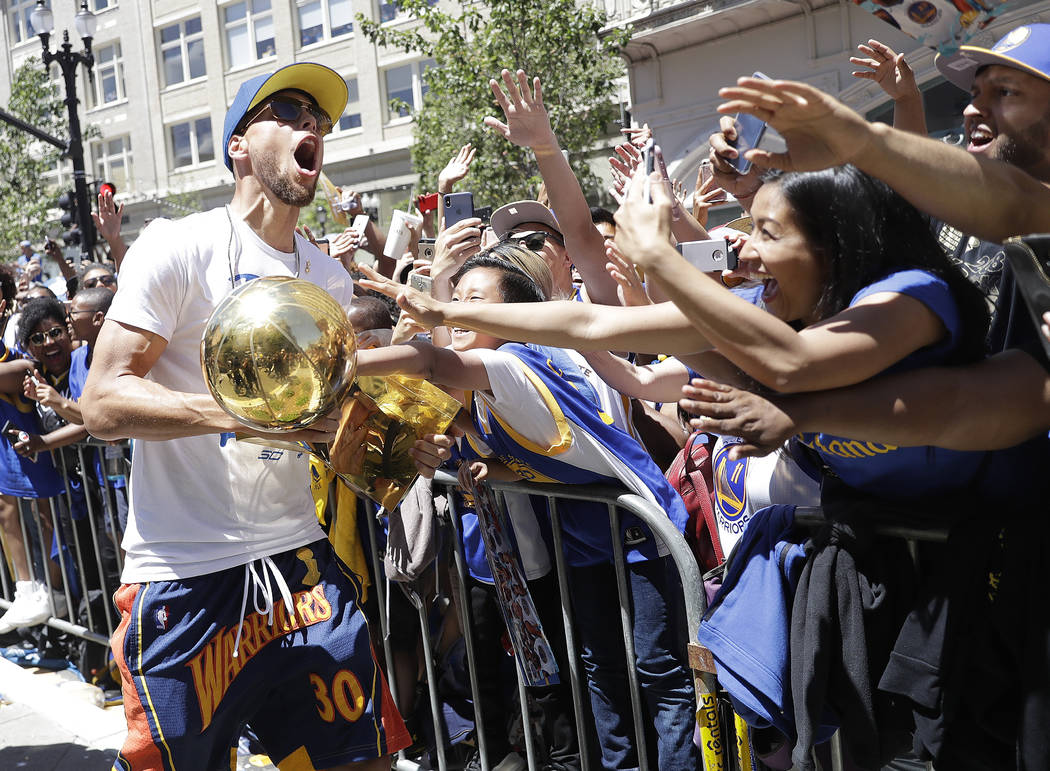 Golden State Warriors' Stephen Curry carries the Larry O'Brien trophy as he celebrates with fans during the team's NBA basketball championship parade, Tuesday, June 12, 2018, in Oakland, Calif. (A ...