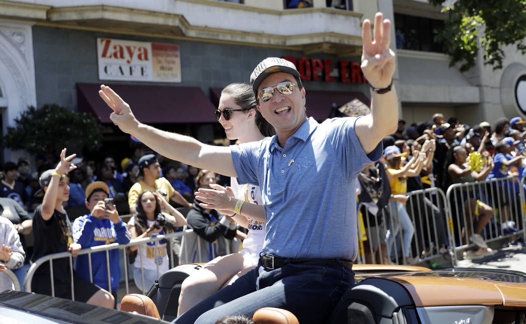 Golden State Warriors owner Joe Lacob waves to fans alongside his daughter Kayci during the team's NBA basketball championship parade, Tuesday, June 12, 2018, in Oakland, Calif. (AP Photo/Marcio J ...