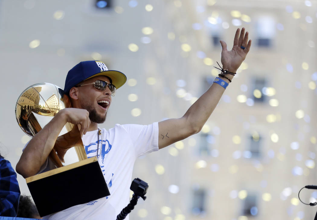 Golden State Warriors' Stephen Curry carries the Larry O'Brien trophy during the team's NBA championship parade, Tuesday, June 12, 2018, in Oakland, Calif. (AP Photo/Marcio Jose Sanchez)
