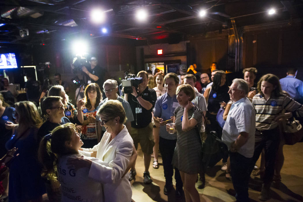 Clark County Commissioner Chris Giunchigliani embraces supporter Marcy Ramirez, lower left, at an election watch party at Bunkhouse Saloon after losing in the Democratic primary for Nevada governo ...