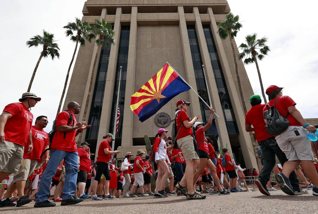 Teachers rally outside of Arizona Gov. Doug Ducey's Executive Tower Monday, April 30, 2018, in Phoenix on their third day of walk outs. Teachers in Arizona and Colorado walked out of their classes ...