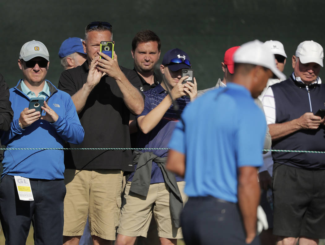 Spectators record imagery of Tiger Woods as he approaches the fourth tee during a practice round for the U.S. Open Golf Championship, Tuesday, June 12, 2018, in Southampton, N.Y. (AP Photo/Julie J ...