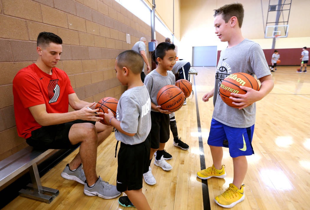Portland Trail Blazers center and Las Vegas Native Zach Collins signs autographs for, from left, Cash Torres, 7, Mason Tsui, 8, and Hudson Dannels, 9, during his basketball camp at Bill and Lillie ...