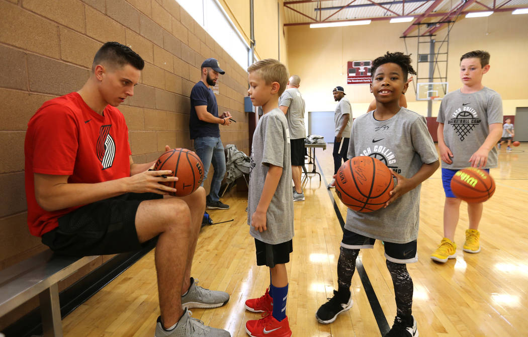 Portland Trail Blazers center and Las Vegas Native Zach Collins signs autographs for, from left, Ty Ahlstrom, 9, Kortell Price, 8, and Hudson Dannels, 9, during his basketball camp at Bill and Lil ...