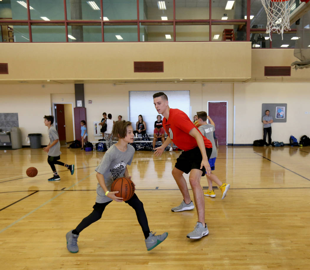 Portland Trail Blazers center and Las Vegas Native Zach Collins runs a drill with Luke Yurik, 14, during his basketball camp at Bill and Lillie Heinrich YMCA in Las Vegas June 12, 2018. K.M. Canno ...