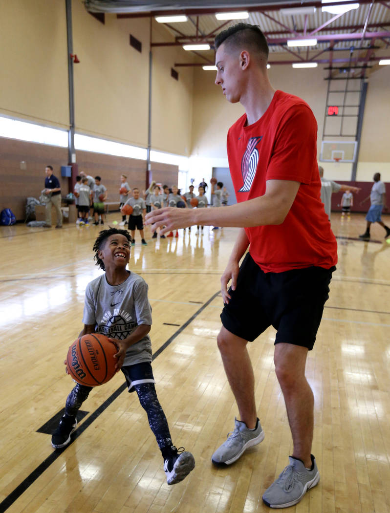 Portland Trail Blazers center and Las Vegas Native Zach Collins runs a drill with Kortell Price, 8, during his basketball camp at Bill and Lillie Heinrich YMCA in Las Vegas June 12, 2018. K.M. Can ...