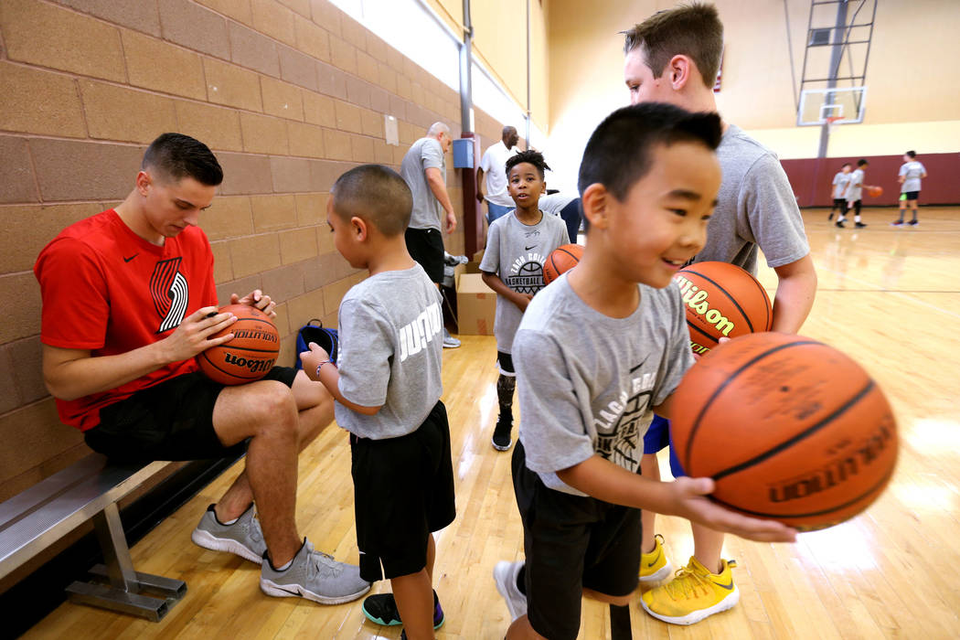 Portland Trail Blazers center and Las Vegas Native Zach Collins signs autographs for, from left, Cash Torres, 7, Kortell Price, 8, Mason Tsui, 8, and Hudson Dannels, 9, during his basketball camp ...