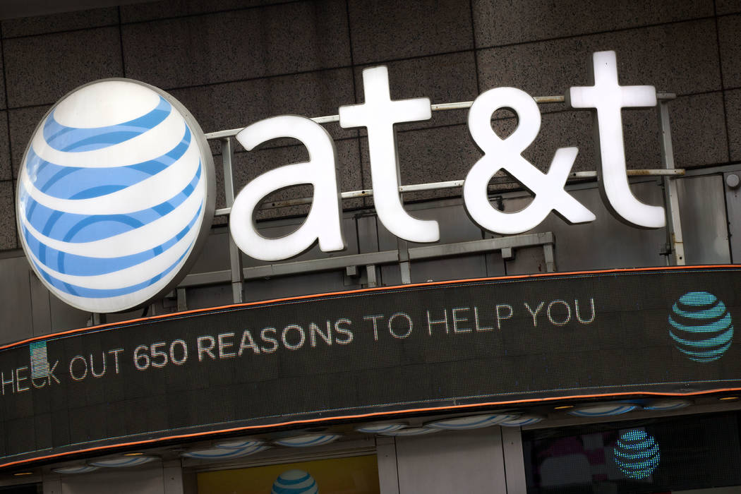 In this Monday, Oct. 24, 2016, file photo, the AT&T logo is positioned above one of its retail stores, in New York. (AP Photo/Mark Lennihan, File)