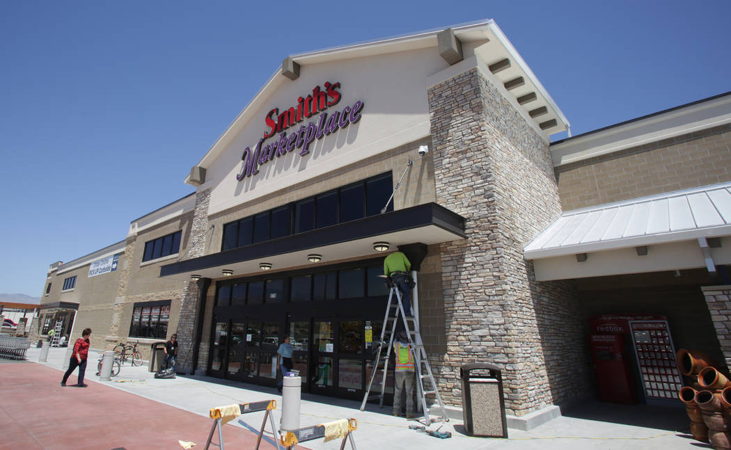Workers from Redd Roofing of Ogden, Utah put final touches on the storefront of the new 125,000-square-foot Smith's Marketplace on Skye Canyon Road on Tuesday, June 12, 2018 the day before ...