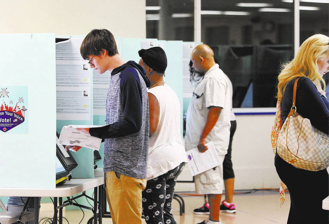 Voters, including Steven Roman, 18, of Las Vegas cast their vote during Tuesday's primary election at a polling station at Kenny G. Guin Middle School on June 12, 2018, in Las Vegas Bizuayehu Tesf ...