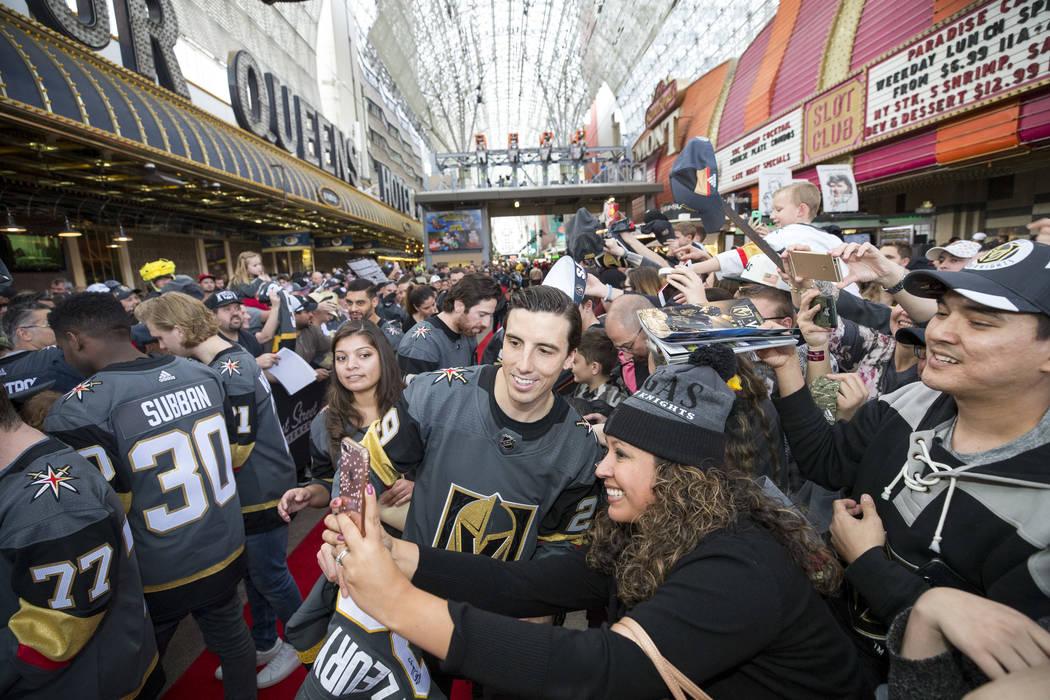 El portero de Vegas Golden Knights Marc-Andre Fleury (29) posa con un fan durante la primera fiesta de fanáticos del equipo en la Fremont Street Experience en el centro de Las Vegas el domingo 14 ...
