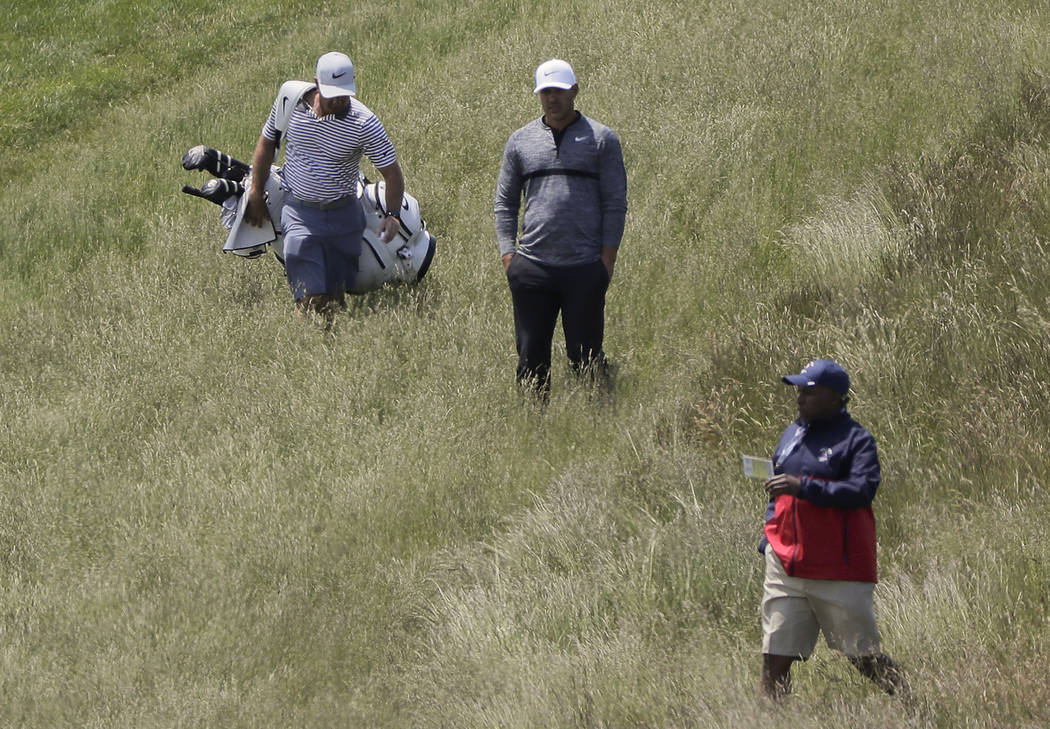 Brooks Koepka, center, lines up a shot from the rough along the 9th fairway during a practice round for the U.S. Open Golf Championship, Monday, June 11, 2018, in Southampton, N.Y. (AP Photo/Julie ...
