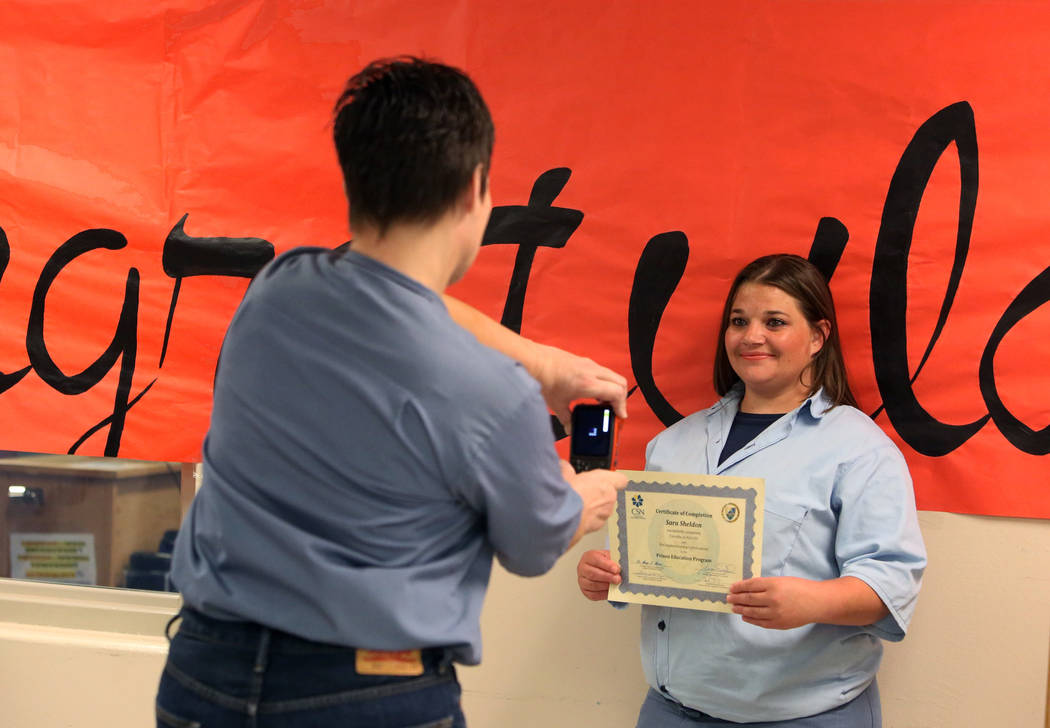 Inmate Sara Sheldon, right, poses for photo with her Academic Life Skill 101 certificate to Amy Bessey, a photographer at the Florence McClure Women's Correctional Center, after a graduation cerem ...