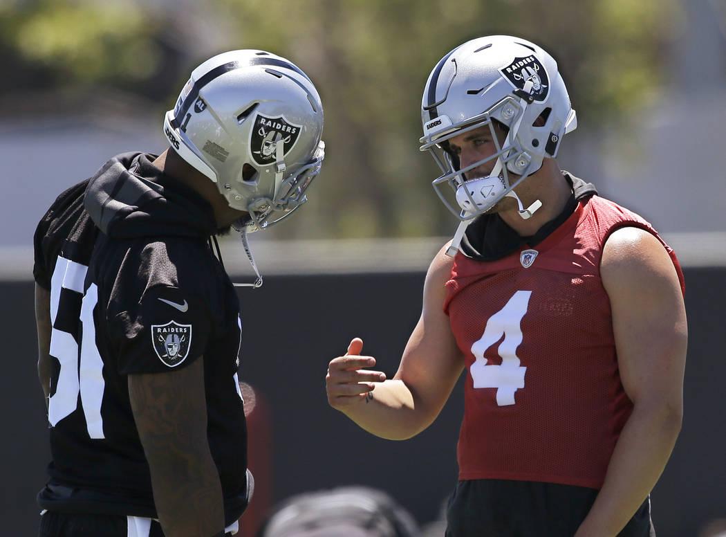 Oakland Raiders linebacker Bruce Irvin, left, talks with quarterback Derek Carr at the NFL football team's minicamp Tuesday, June 12, 2018, in Alameda, Calif. (AP Photo/Rich Pedroncelli)