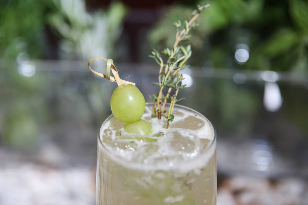 A Grape Thymes cocktail is served with Alexander Grappa, Italicus, grilled lemon sour, amaretto, San Pellegrino Limonata, grapes, and a sprig of thyme, at Pizzeria Monzú in Las Vegas, Tuesday, Ju ...