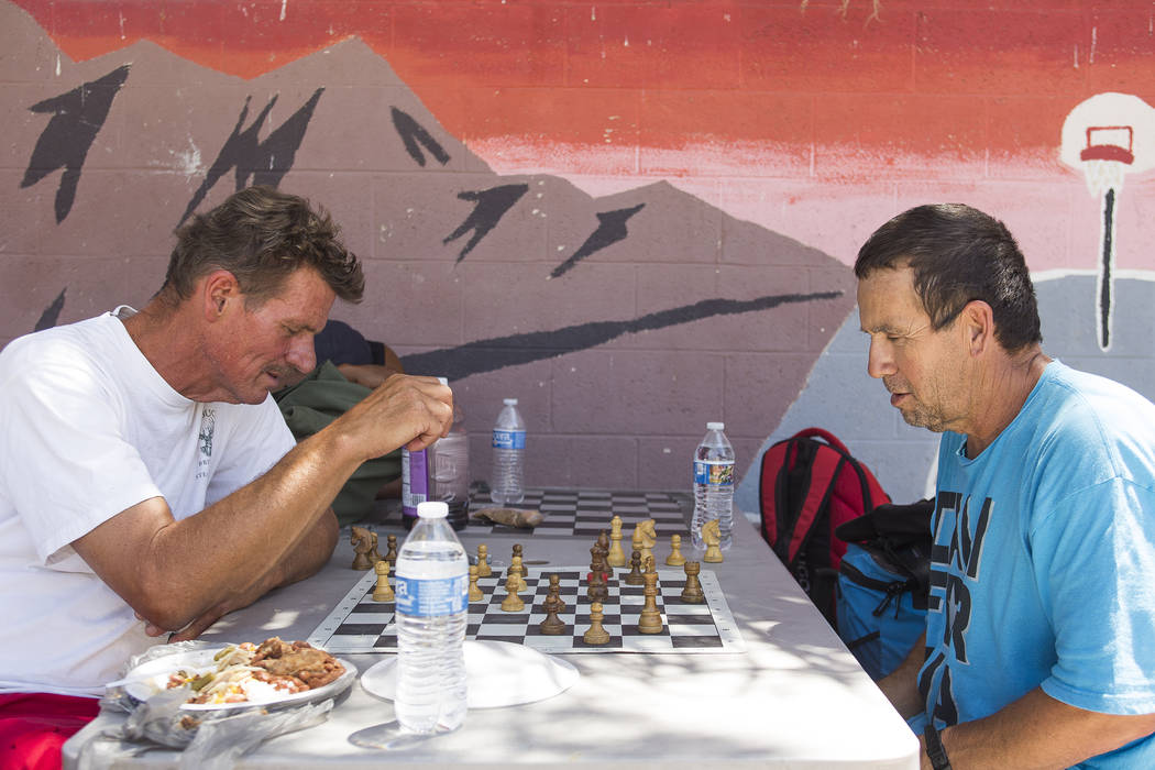 William Breland, left, plays chess with Larry Spellman in the shade at the Courtyard Homeless Resource Center in Las Vegas, Wednesday, June 13, 2018. Rachel Aston Las Vegas Review-Journal @rookie__rae