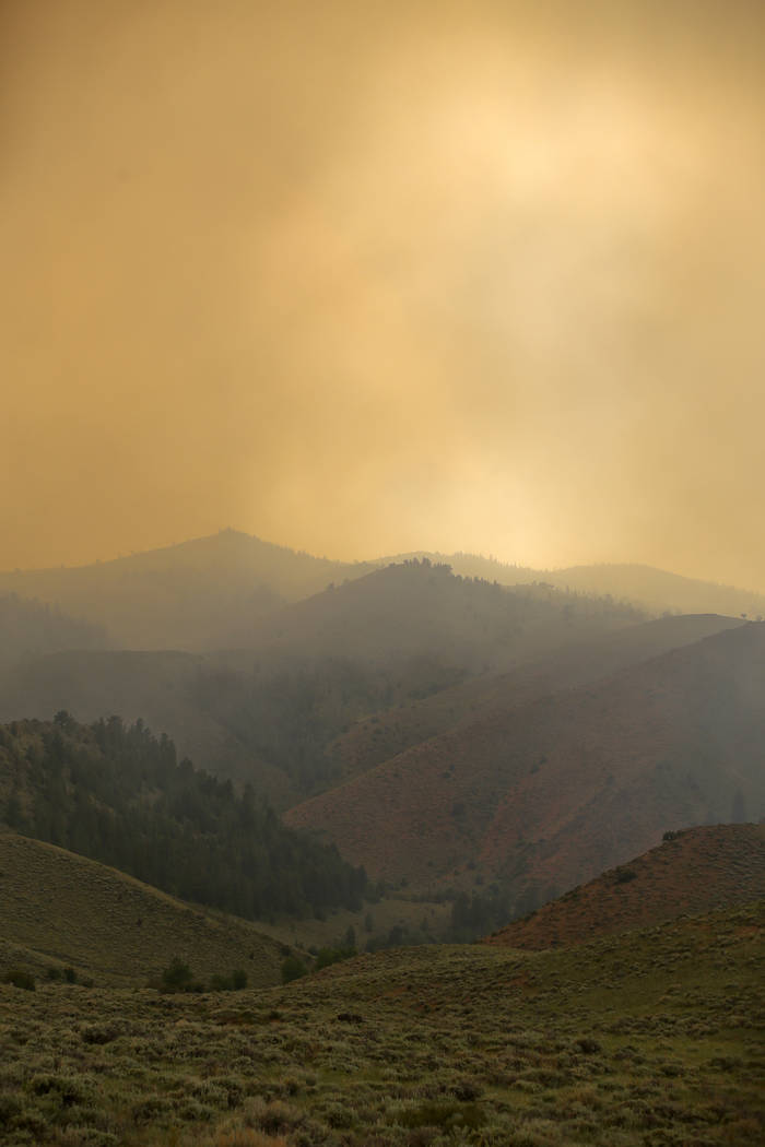 Smoke from the Badger Creek Fire drifts through the air, Monday, June 11, 2018, as seen from Highway 10, near Woods Landing, Wyo. (Shannon Broderick/Laramie Boomerang via AP)