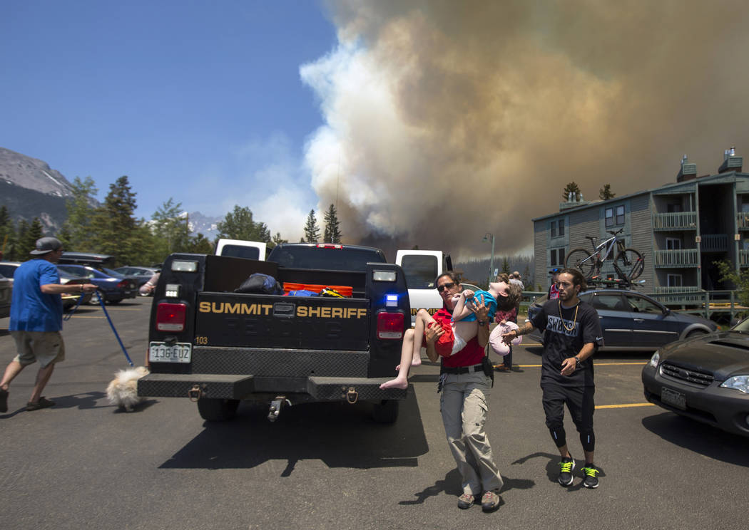 Erin Sirek with the Summit County Sheriff's Department Residents carries a boy as residents evacuate their homes from a wild fire approaching in the Wildernest neighborhood near Silverthorne, Colo ...