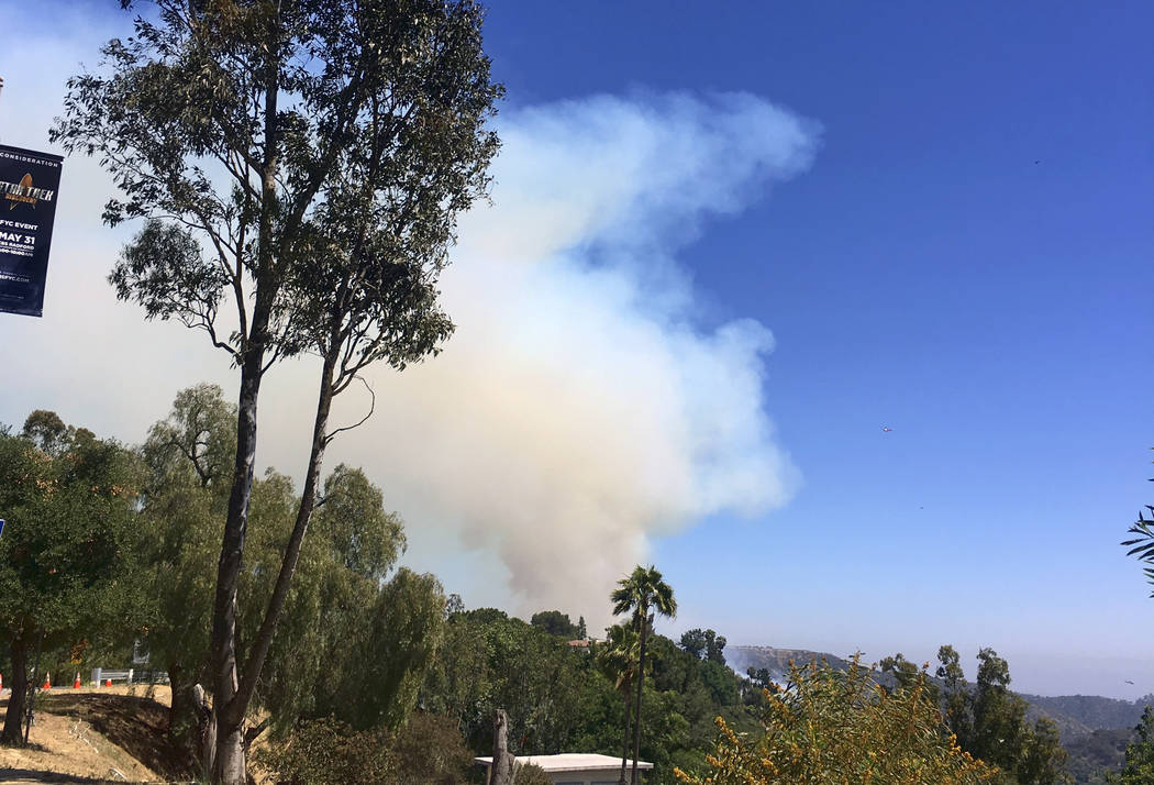A large plume of smoke rises over Benedict Canyon in Los Angeles in the hills surrounded by Beverly Hills, Calif., on Tuesday, June 12, 2018. More than 100 firefighters raced to the hills overlook ...