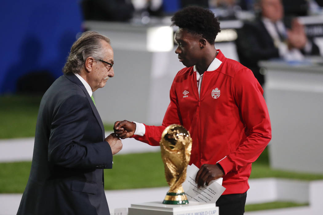 Decio de Maria, President of the Football Association of Mexico, left, and Canadian soccer player Alphonso Davies, right, present a joint United bid by Canada, Mexico and the United States to host ...