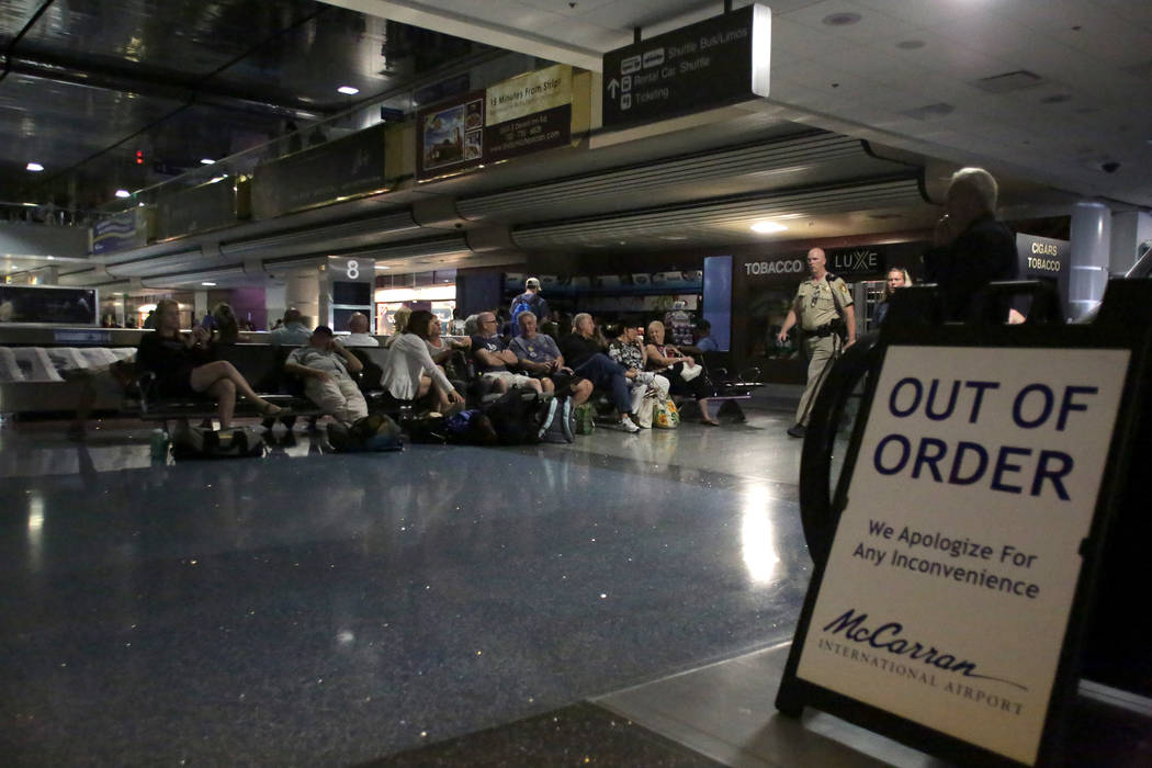 A sign blocks the escalator in McCarran International Airport's baggage claim as travelers wait out a power outage in Terminal 1 on Wednesday, June 13, 2018. Michael Quine Las Vegas Reviewj ...