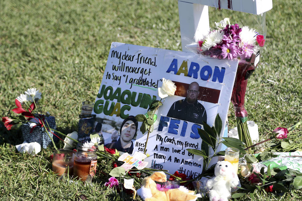 In this Feb. 16, 2018 file photo, a tribute to student Joaquin Oliver and coach Aaron Feis is left at the base of a white cross at Pine Trails Park in Parkland, Fla. (Amy Beth Bennett/South Florid ...