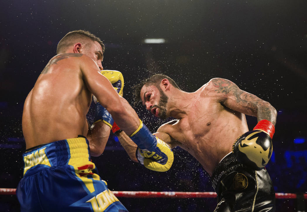 Vasiliy Lomachenko, left, of Ukraine, tries to avoid a punch from Jorge Linares, of Venezuela, during the WBA lightweight championship boxing match Saturday, May 12, 2018, in New York. (AP Photo/K ...