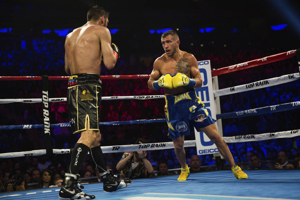 Vasiliy Lomachenko, of Ukraine, at right, fights Jorge Linares, of Venezuela, during their WBA World Title lightweight boxing bout Saturday, May 12, 2018, in New York. (AP Photo/Kevin Hagen)