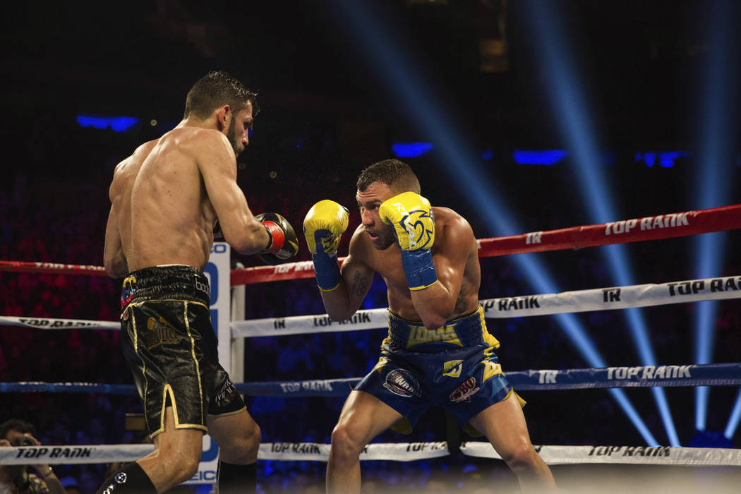 Vasiliy Lomachenko, right, of Ukraine, covers up against Jorge Linares, of Venezuela, during their WBA lightweight championship boxing match Saturday, May 12, 2018, in New York. (AP Photo/Kevin Hagen)