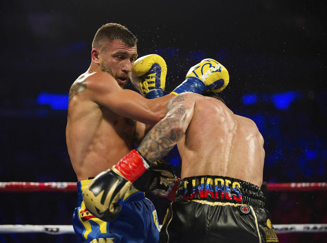 Vasiliy Lomachenko, left, of Ukraine, at left, throws a right at Jorge Linares, of Venezuela, during their WBA lightweight championship boxing match Saturday, May 12, 2018, in New York. (AP Photo/ ...