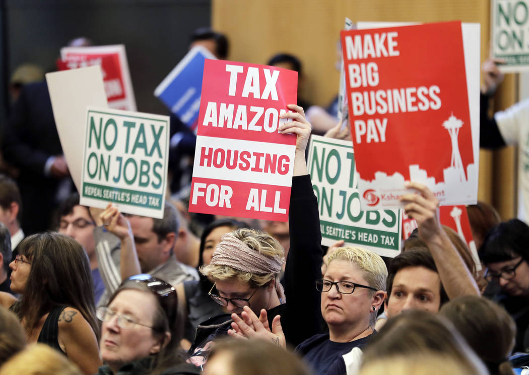 "People attending a Seattle City Council meeting hold signs that read ""Tax Amazon, Housing for All,"" and ""No Tax on Jobs"" listen to public comment on the debate over a possible ..."