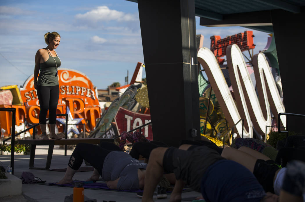 Yoga instructor Eileen Lorraine, left, leads a hot yoga session in the outdoor Neon Boneyard area at the Neon Museum in Las Vegas on Wednesday, July 19, 2017. Three more one-hour sessions are slat ...