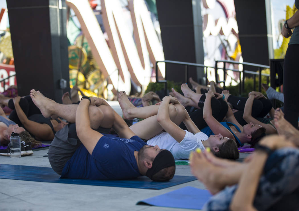 People participate in a hot yoga session in the outdoor Neon Boneyard area at the Neon Museum in Las Vegas on Wednesday, July 19, 2017. Three more one-hour sessions are slated to take places on We ...