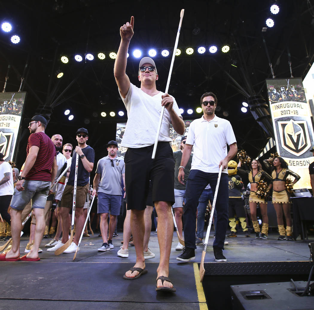 """Golden Knights defenseman Nate Schmidt, center, and right wing Alex Tuch, right, look to the crowd to hand out hockey sticks during the """"Stick Salute to Vegas and Our Fans"""" held by the G ..."""