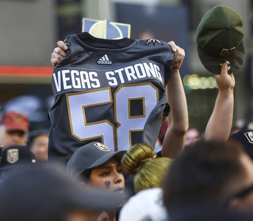 """A Golden Knights fan holds up a jersey honoring the 58 people killed in the Oct. 1 shooting during the """"Stick Salute to Vegas and Our Fans"""" held by the Golden Knights at the 3rd Street S ..."""