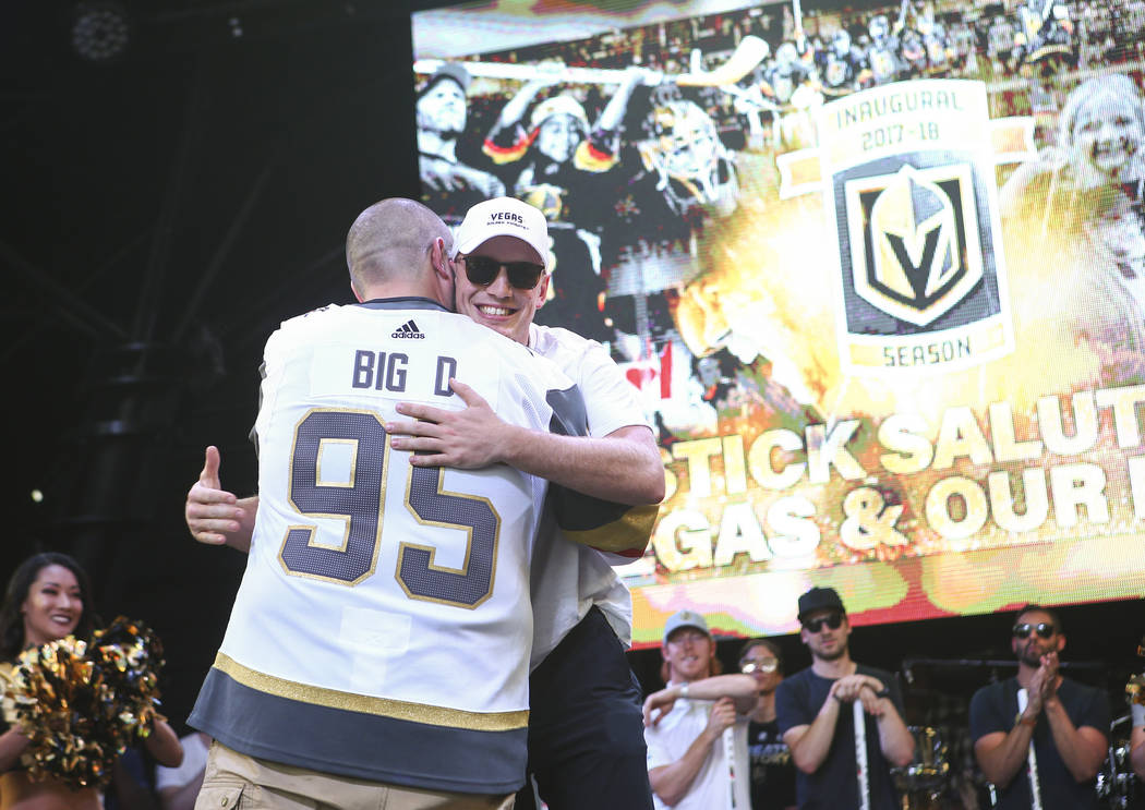 "Golden Knights defenseman Nate Schmidt hugs announcer Wayne ""Big D"" Danielson during the ""Stick Salute to Vegas and Our Fans"" held by the Golden Knights at the 3rd Street Stage ..."