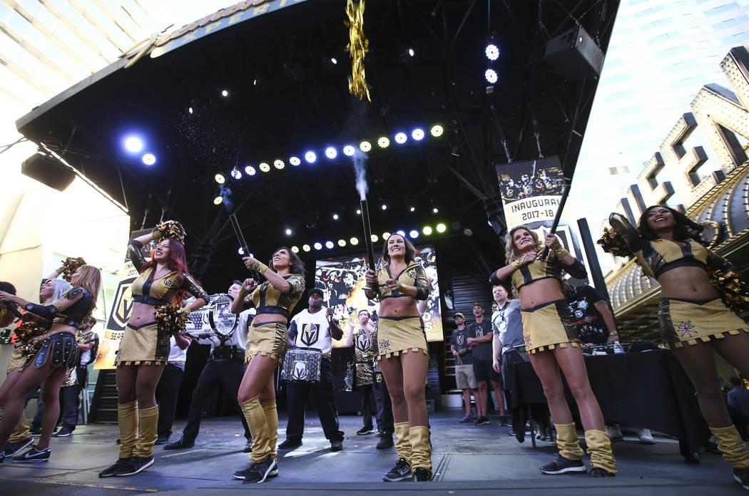 "Members of the Golden Aces cheer during the ""Stick Salute to Vegas and Our Fans"" held by the Golden Knights at the 3rd Street Stage at the Fremont Street Experience in downtown Las Vegas ..."
