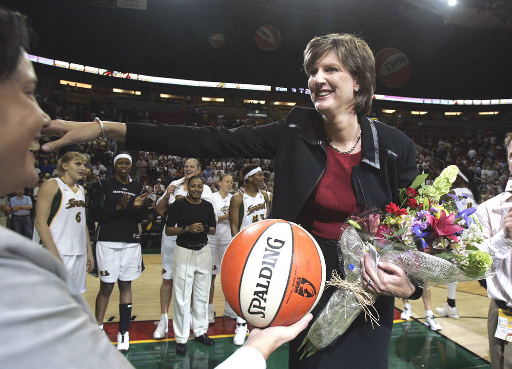 Seattle Storm coach Anne Donovan, right, smiles as she is handed the game ball by team official Karen Bryant following the Storm's victory over the Minnesota Lyn in Seattle in 2005. (AP Photo/Ela ...