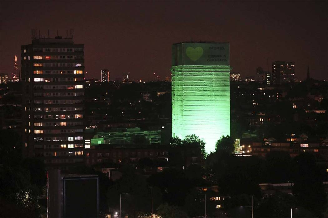 Grenfell Tower in west London is illuminated in green to mark a year since a devastating fire took hold, claiming 72 lives, Thursday June 14, 2018. (Jonathan Brady/PA via AP)