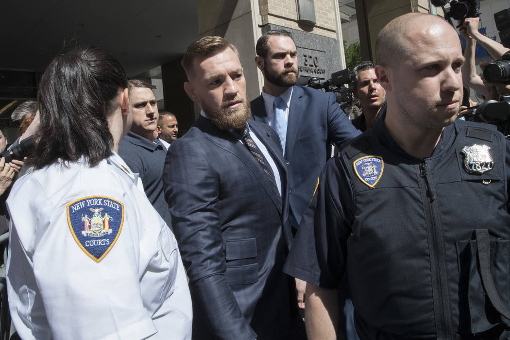 Mixed martial arts figher Conor McGregor, center, is escorted by court officers as he leaves a Brooklyn Supreme court, Thursday, June 14, 2018, in New York. (AP Photo/Mary Altaffer)