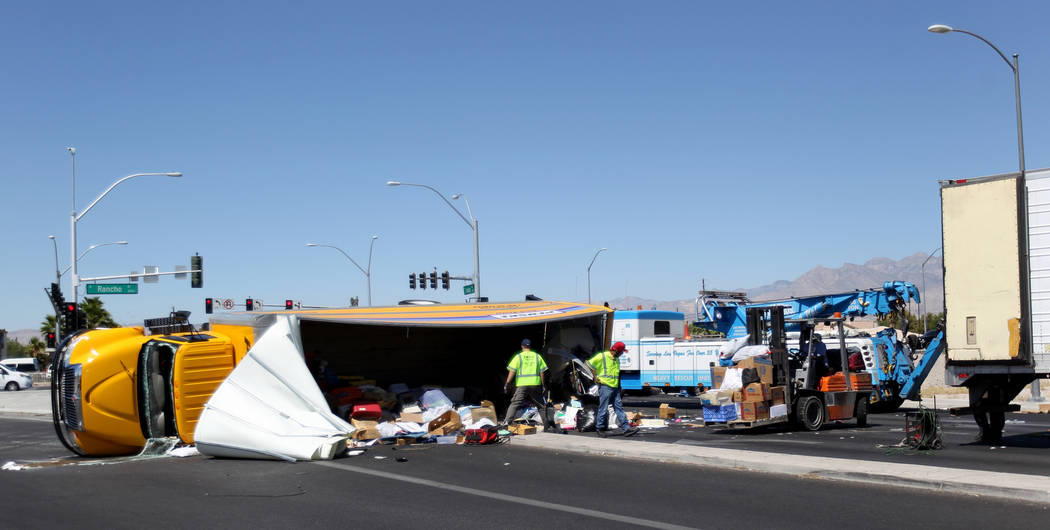 Workers transfer the contents of a moving truck after it crashed on Decatur Boulevard near North Rancho Drive Thursday, June 14, 2018. North Las Vegas Police said the occupants sustained minor inj ...