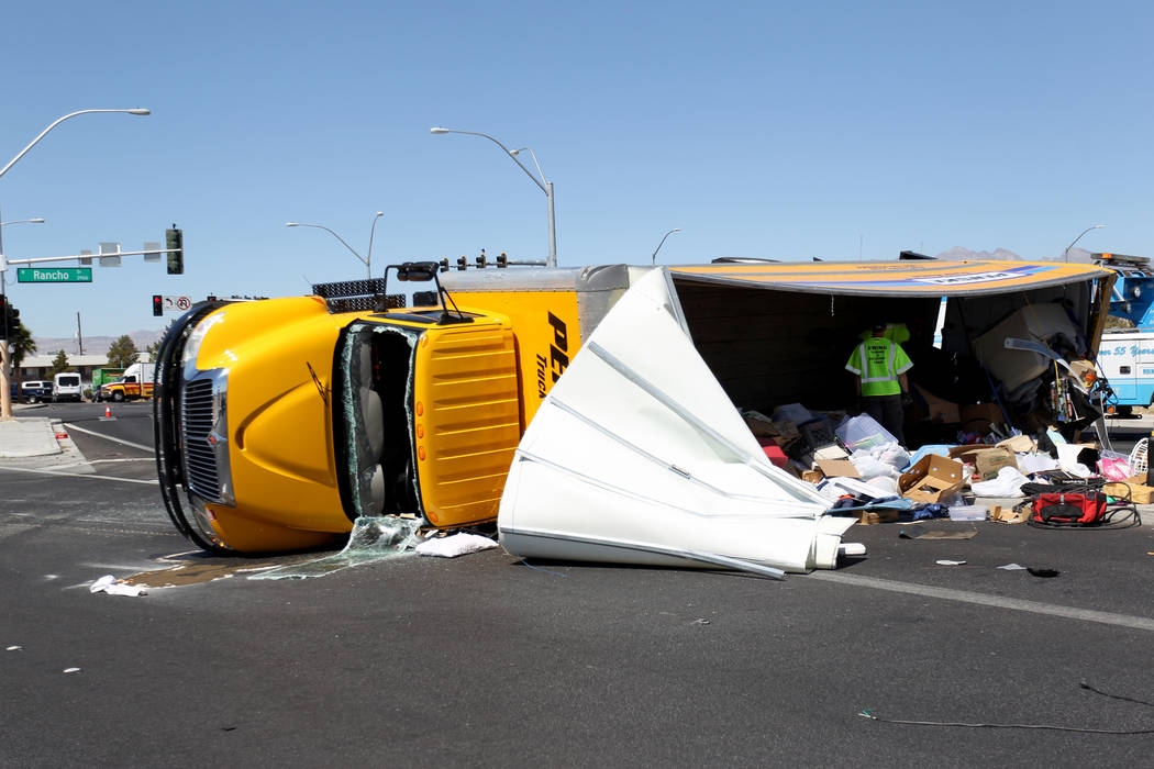 Workers transfer the contents of a moving truck after it crashed on Decatur Boulevard near North Rancho Drive, Thursday, June 14, 2018. North Las Vegas police said the occupants sustained minor in ...
