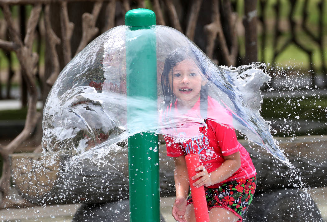 Layla Valdivia, 6, playing recently at Sunset Park, has the right idea on how to cool off as temperatures remain in triple digits. (Bizuayehu Tesfaye/Las Vegas Review-Journal) @bizutesfaye