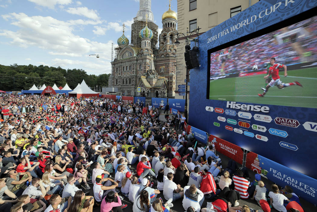 People watch on a huge screen the 2018 soccer World Cup match between Russia and Saudi Arabia at a fan zone in St.Petersburg, Russia, Thursday, June 14, 2018. (AP Photo/Dmitri Lovetsky)