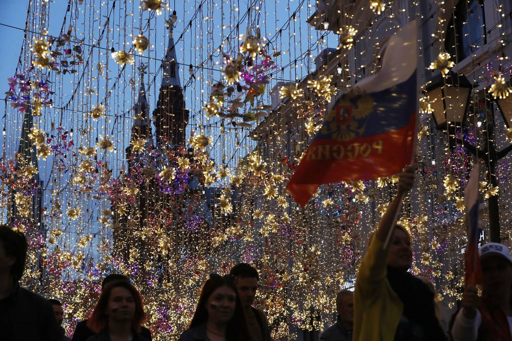 People carry flags as Russians celebrate in Nikolskaya street after their team defeated Saudi Arabia 5-0 in the opening match of the 2018 soccer World Cup, in Moscow, Russia, Thursday, June 14, 20 ...