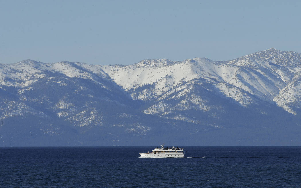In this March 5, 2018 file photo snow covers the mountain tops as a boat crosses Lake Tahoe, in South Lake Tahoe, Calif. (AP Photo/Rich Pedroncelli,File)