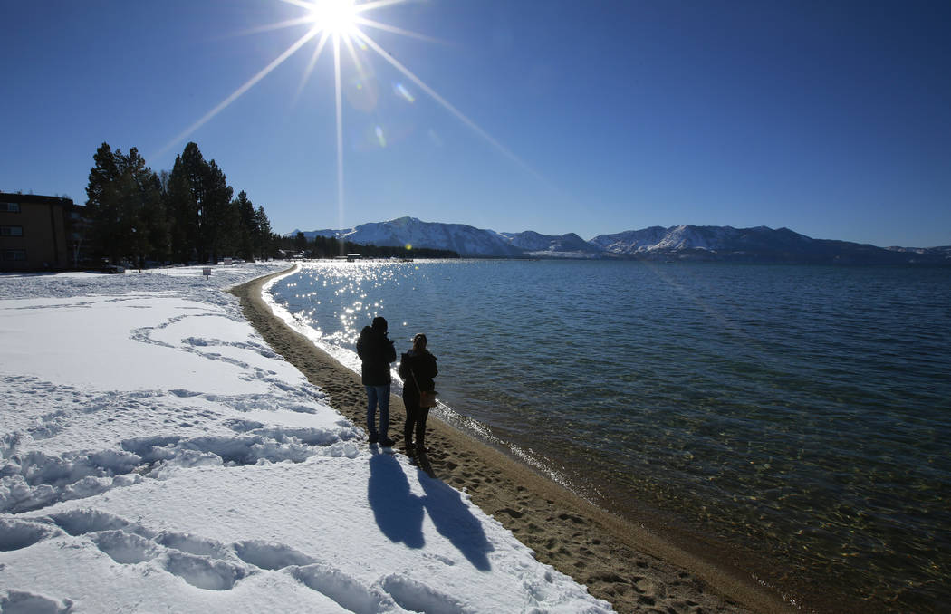 In this March 5, 2018 file photo sunlight shimmers off the snow and waters of Lake Tahoe in South Lake Tahoe, Calif. (AP Photo/Rich Pedroncelli,File)