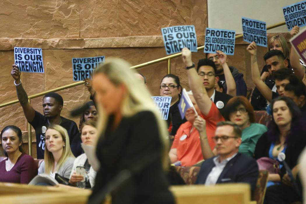 Aimee Hairr speaks as members of the audience hold up signs in support during public comment about an agenda item on whether or not to direct a gender-diverse policy for the school district during ...